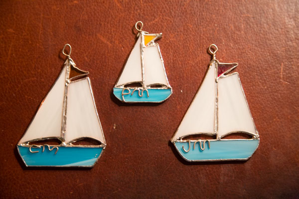 Three homemade stained glass sailboat ornaments