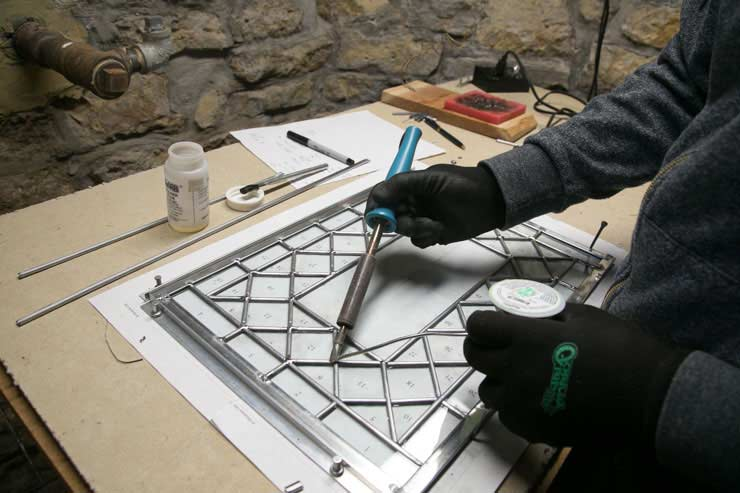 Soldering the final touches on a glass panel